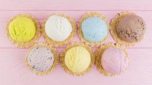 Bochas de helados de colores sobre mesa rosada