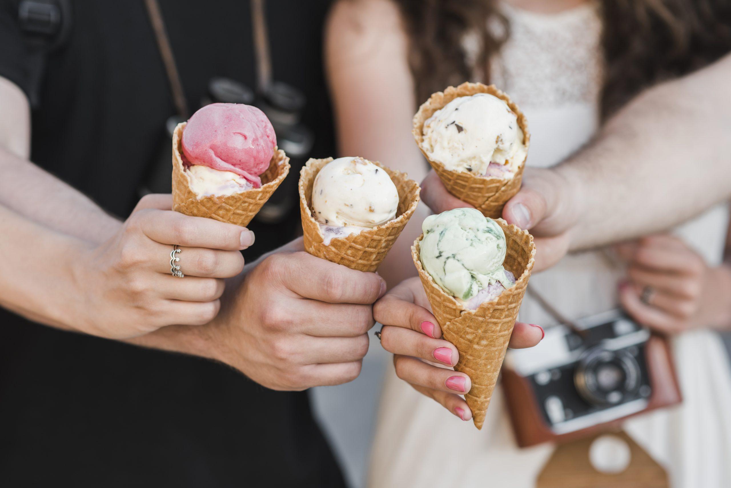 Manos sostiendo conos de helados